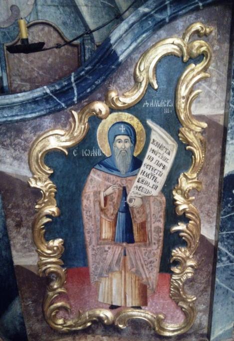 """Damaszkuszi Szent János képmása az énekespulton A kezében tartott tekercsen a Szent János által szerzett ünnepi kánon egy részlete: """"Itt halott asszonynak, természetfölötti módon azonban Isten Atyjának néztek Téged, [Tisztaságos, a dicsőséges apostolok, s remegő kézzel érintettek meg, látva, hogy dicsfényben ragyogsz, Te, Istent befogadó sátor."""" (3. óda, tropárion)."""